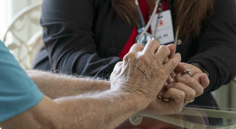 A nurse holding a residents hand