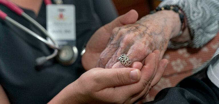 Nursing holding residents hand