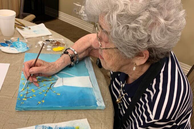 Senior Woman Painting Flowers In Vase At Class