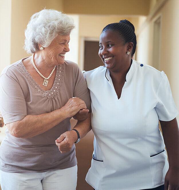 Resident Holding Arm Of Senior Woman Walking Down Hall